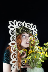 Woman with red hair posing with picture frame and yellow flowers