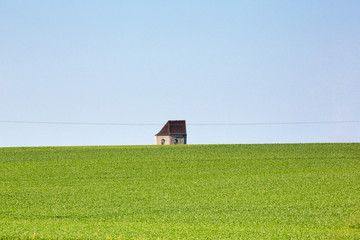 Green grass, blue sky and a small tiny old house