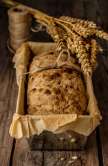 Rustic bread in baking tin on vintage wood