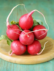 bunch of fresh organic radishes on wooden plate