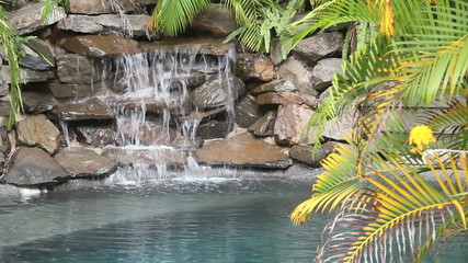 Water falling on rocks in a poolside water feature.