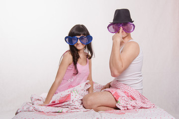 Young couple sitting bed with big glasses, guy in hat