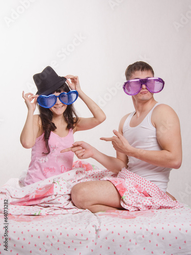 Young couple sitting in bed with big glasses