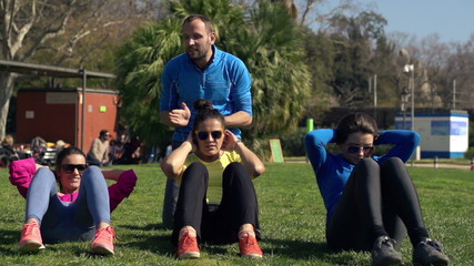 Young women doing sit ups with personal trainer in the park