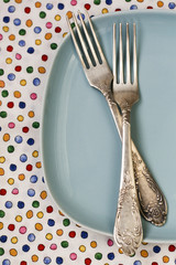 Two forks lying on blue plate on bright background
