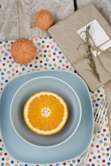 Juicy orange on blue plate is the old pad and tangles of yarn