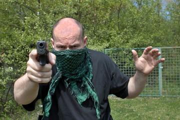 Masked man aims with gun