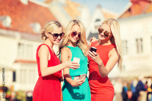 beautiful girls with smartphones in the city