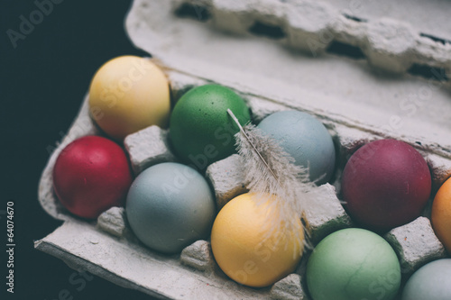 pastel colored easter eggs with feather
