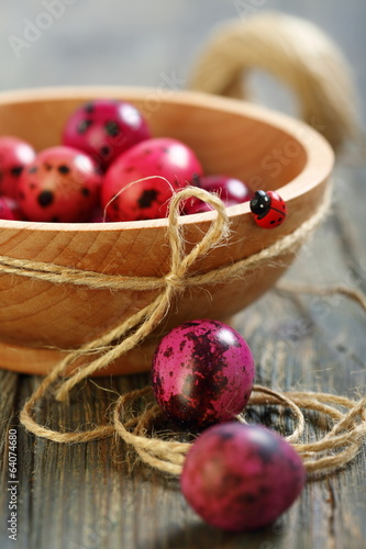 Easter eggs and wooden bowl with ladybug.