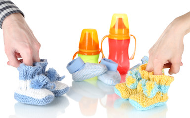 Hands with crocheted booties for baby, isolated on white