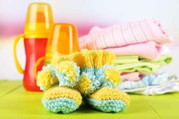 Composition with crocheted booties for baby,clothes, bottles