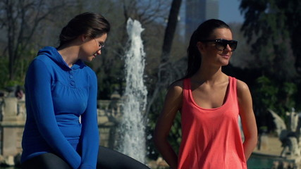 Sporty girlfriends resting after jogging, super slow motion
