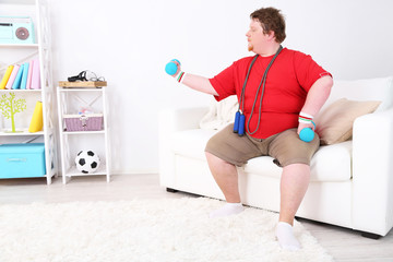 Large fitness man making exercises with dumbbells, at home