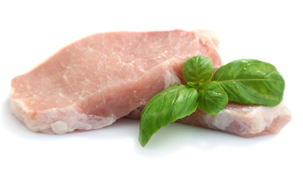 Raw meat steaks with basil isolated on white