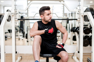 Man working out at gym, resting at  bench press