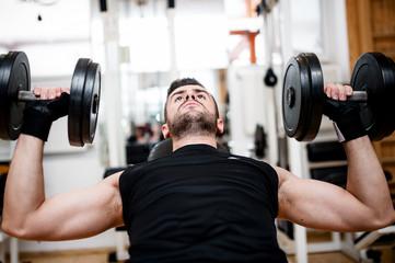 bodybuilder training in the gym: chest - dumbbell bench press