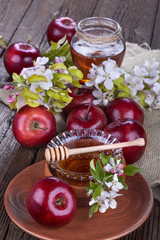 apples in a bowl with honey and apple flower on wooden table