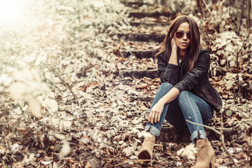 Sexy woman in sunglasses posing in a park