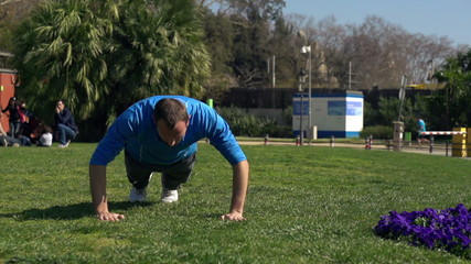 Young man doing press ups in the park