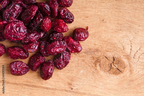 Diet food. Border of dried cranberries on wooden background
