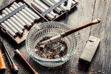 Glass ashtray with thin wooden pipes, cigarettes and lighter aro