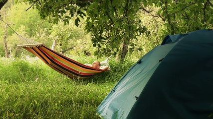 Happy man relaxing in hammock in Summer camp