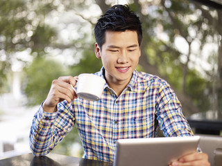 young man using tablet computer drinking coffee
