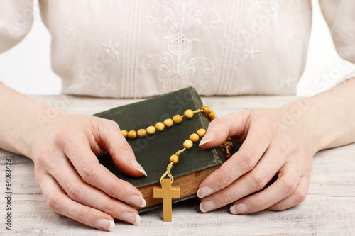 Woman holding wooden rosary and Holy Bible.