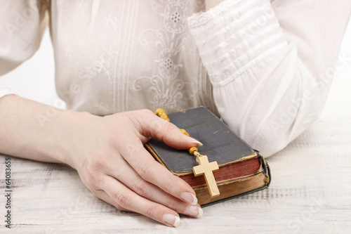Woman holding Holy Bible and wooden rosary