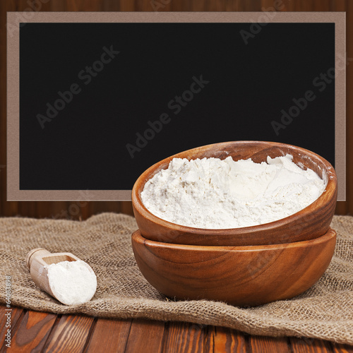 Flour in wooden bowl with place for text.