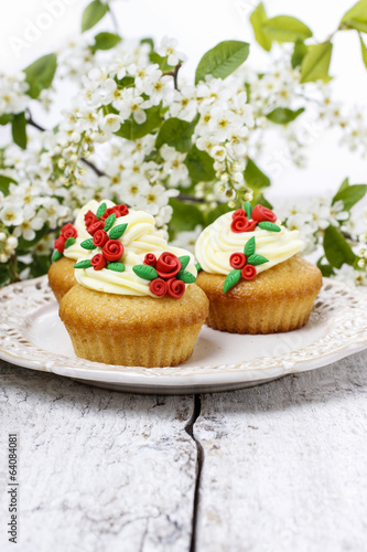 Beautiful rose cupcake and bird cherries in the background