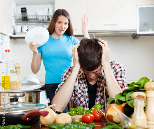 Sad man with angry wife at kitchen