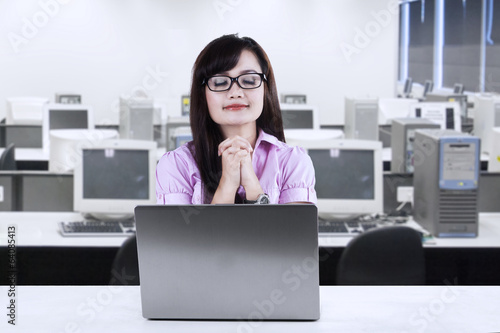 Young businesswoman praying at office