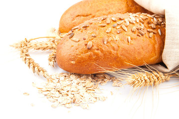 Loaf of bread with oat flakes, spikelets of wheat on white,