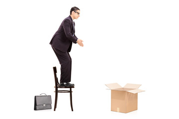 Male businessman prepared to jump in an empty box