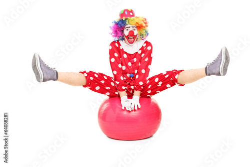Male clown performing on a pilates ball
