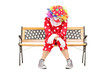 Sad clown sitting on a wooden bench