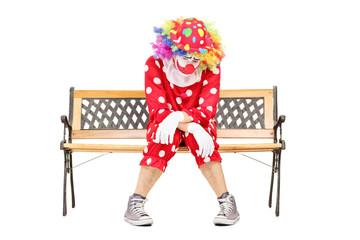Sad clown sitting on a wooden bench