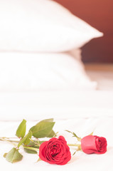 Romantic getaway with red roses on bed