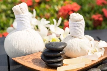 Herbal spa massage with hot compress balls and stacked stones