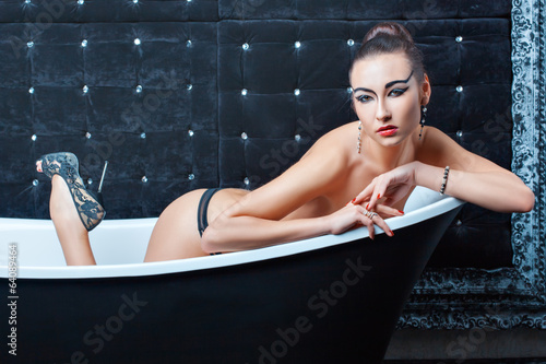 Girl lying in a bathtub.