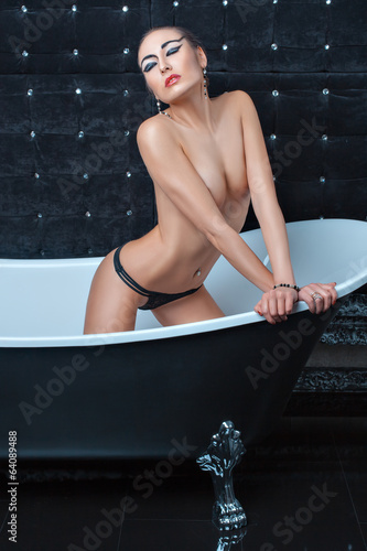 Girl sitting in a bathtub.