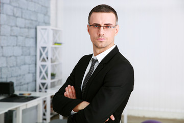 Confident businessman with arms folded standing in office