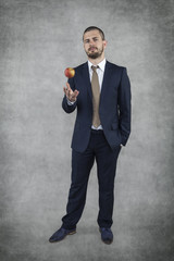 businessman tossing an apple