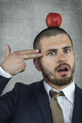 businessman with an apple on his head ready to commit suicide