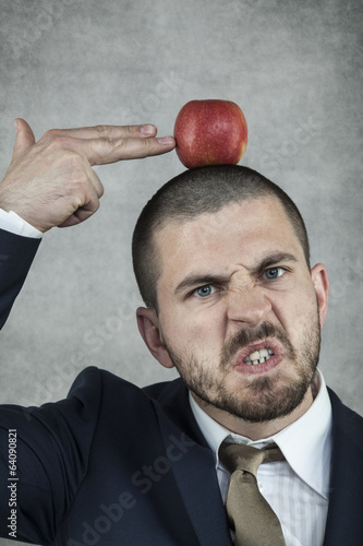 Businessman aiming a gun with his hand in the apple
