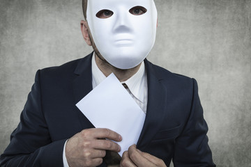 Businessman in a mask hiding bribe