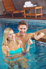 Smiling couple in pool holding thumbs up