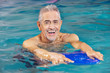 Senior man with kickboard in swimming pool